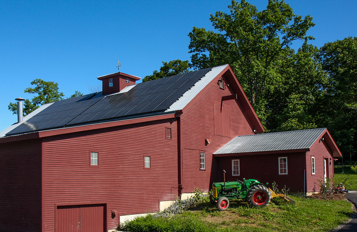 Large red barn with solar panels on the roof