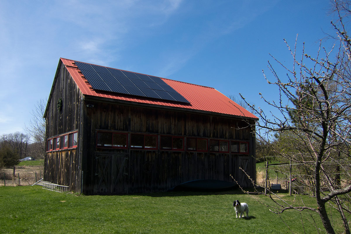 Large wooden barn with red roof and solar panels on top