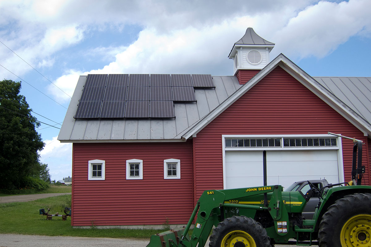 Barn with solar on the roof and a tractor out front