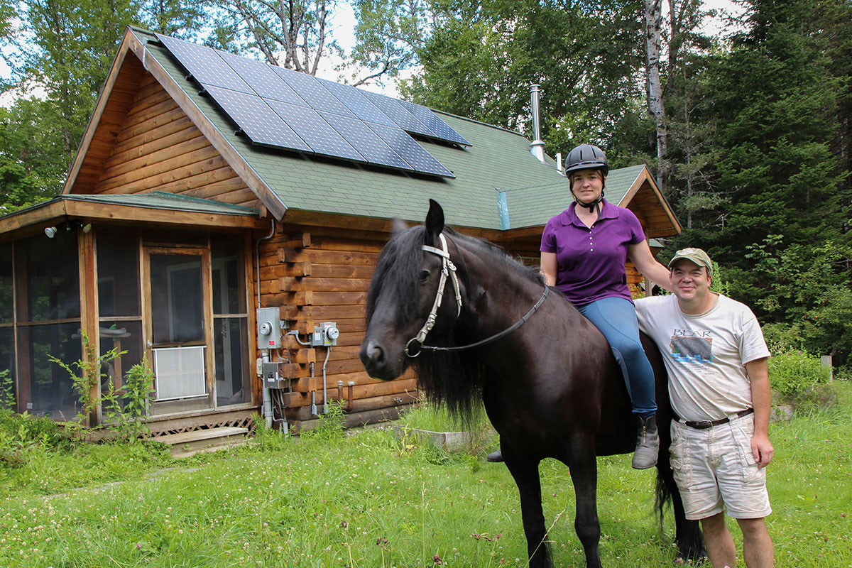Vermont cabin with solar panels on the roof and happy solar homeowners