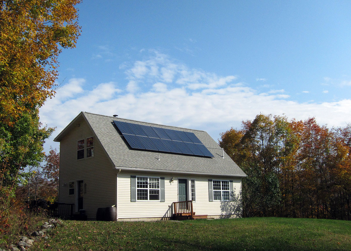 Cape style home with solar panels on roof