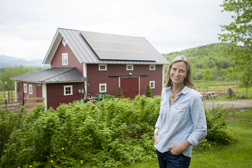 SunCommon homeowner in front of her solar barn
