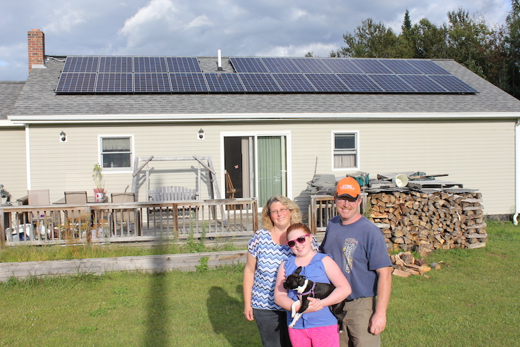 Family in East Burke standing in front of their solar home